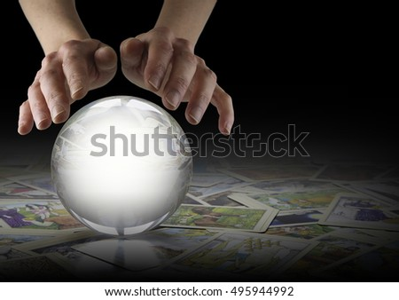 Crystal Ball Reading and Tarot Cards - Hands hovering over a large clear Crystal Ball on a dark background with tarot cards scattered randomly beneath and copy space to right #495944992