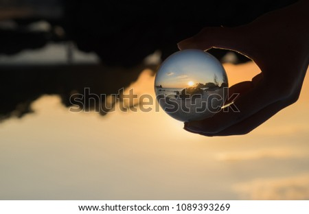 Crystal Ball Reflecting the evening sunset beach. subject is blurred. #1089393269