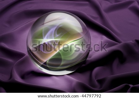 Crystal ball with colorful smoky interior shot on purple satin background