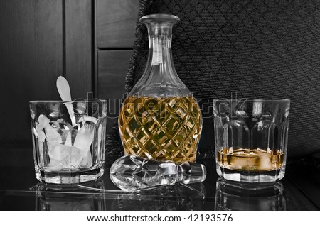 Crystal bottle and glass of old scotch with ice on a bar