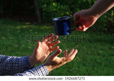 Crystal clean water puring to metal cup in hand slow motion. Thirst quench concept. #1426687271