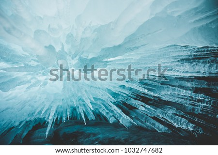 Crystal clear sharp icicles hanging down in frozen cave, lake Baikal, Olkhon island, Siberia, Russia. Beautiful winter wallpaper.