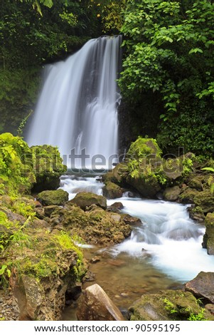 Crystal clear water tumbles down a tropical waterfall in Arenal National Park in Costa RIca