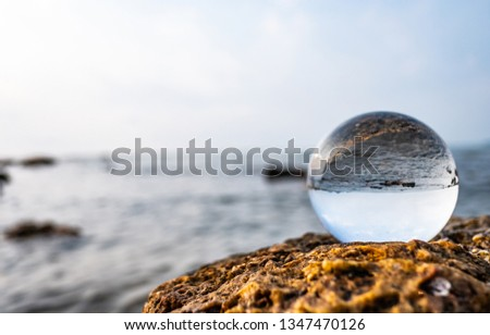 Crystal glass balls are displayed on a rocky coast with turquoise clouds covered with a summer background. Can be used for displaying or editing your background products Business travel #1347470126