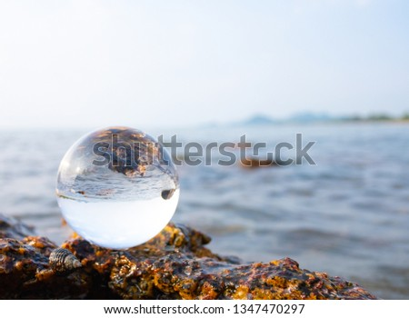 Crystal glass balls are displayed on a rocky coast with turquoise clouds covered with a summer background. Can be used for displaying or editing your background products Business travel #1347470297