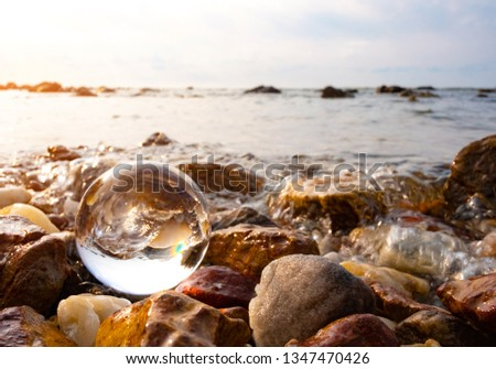 Crystal glass balls are displayed on a rocky coast with turquoise clouds covered with a summer background. Can be used for displaying or editing your background products Business travel #1347470426