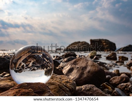 Crystal glass balls are displayed on a rocky coast with turquoise clouds covered with a summer background. Can be used for displaying or editing your background products Business travel #1347470654