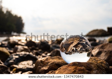 Crystal glass balls are displayed on a rocky coast with turquoise clouds covered with a summer background. Can be used for displaying or editing your background products Business travel #1347470843