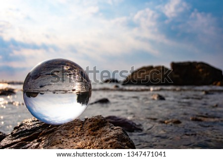Crystal glass balls are displayed on a rocky coast with turquoise clouds covered with a summer background. Can be used for displaying or editing your background products Business travel #1347471041