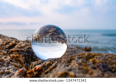 Crystal glass balls are displayed on a rocky coast with turquoise clouds covered with a summer background. Can be used for displaying or editing your background products Business travel #1347471341