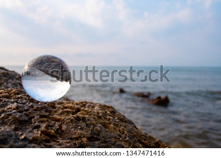 Crystal glass balls are displayed on a rocky coast with turquoise clouds covered with a summer background. Can be used for displaying or editing your background products Business travel #1347471416