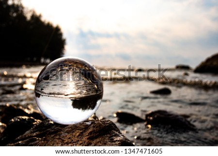 Crystal glass balls are displayed on a rocky coast with turquoise clouds covered with a summer background. Can be used for displaying or editing your background products Business travel #1347471605