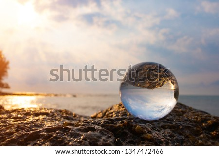 Crystal glass balls are displayed on a rocky coast with turquoise clouds covered with a summer background. Can be used for displaying or editing your background products Business travel #1347472466