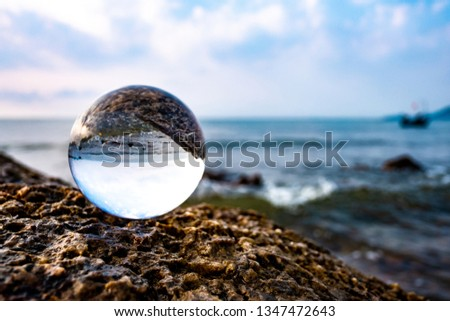 Crystal glass balls are displayed on a rocky coast with turquoise clouds covered with a summer background. Can be used for displaying or editing your background products Business travel  #1347472643