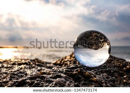 Crystal glass balls are displayed on a rocky coast with turquoise clouds covered with a summer background. Can be used for displaying or editing your background products Business travel #1347473174