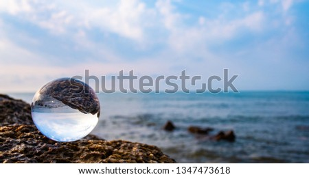 Crystal glass balls are displayed on a rocky coast with turquoise clouds covered with a summer background. Can be used for displaying or editing your background products Business travel #1347473618