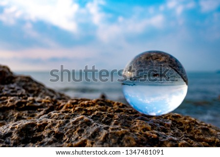 Crystal glass balls are displayed on a rocky coast with turquoise clouds covered with a summer background. Can be used for displaying or editing your background products Business travel #1347481091