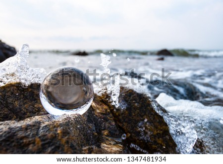 Crystal glass balls are displayed on a rocky coast with turquoise clouds covered with a summer background. Can be used for displaying or editing your background products Business travel #1347481934
