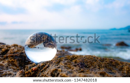 Crystal glass balls are displayed on a rocky coast with turquoise clouds covered with a summer background. Can be used for displaying or editing your background products Business travel #1347482018