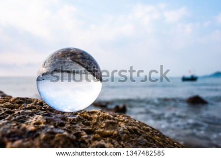Crystal glass balls are displayed on a rocky coast with turquoise clouds covered with a summer background. Can be used for displaying or editing your background products Business travel #1347482585