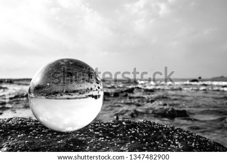 Crystal glass balls are displayed on a rocky coast with turquoise clouds covered with a summer background. Can be used for displaying or editing your background products Business travel #1347482900
