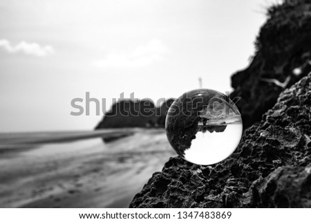 Crystal glass balls are displayed on a rocky coast with turquoise clouds covered with a summer background. Can be used for displaying or editing your background products Business travel #1347483869