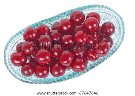 Crystal glass bowl full of fresh cherries isolated on white