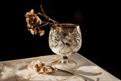 Crystal glass with a dry flower on a white tablecloth and on a black background. Minimalistic still life.