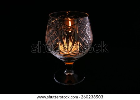 Crystal glass with a lit candle inside #260238503