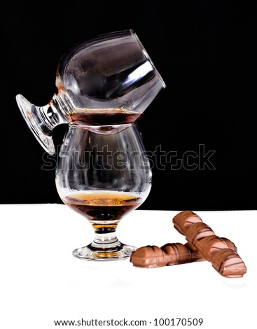 Crystal glass with cognac, chocolate - stock photo