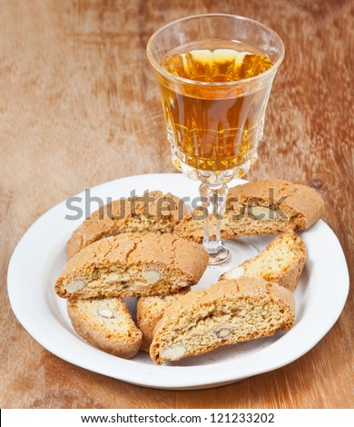 crystal glass with sweet white wine and italian almond cantuccini on saucer on wooden table