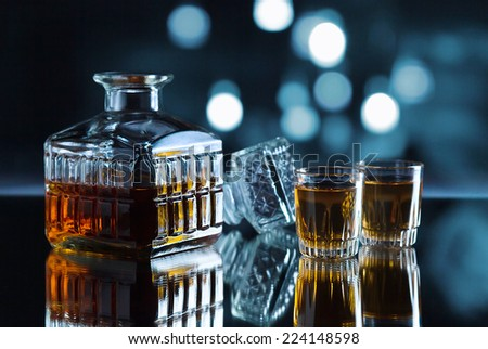 crystal glasses with whiskey on a dark background