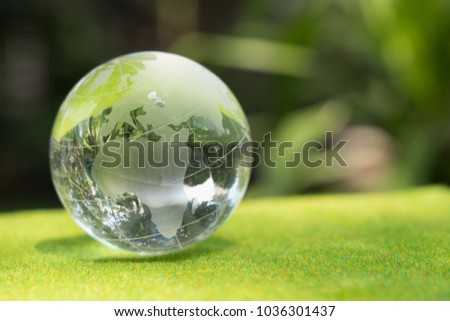 Stock Photo crystal globe on a glass in a nature for environment concept
