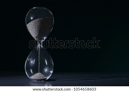 Crystal hourglass on dark background. Time management concept