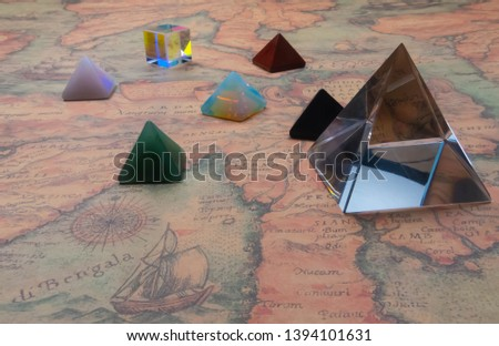 Crystal pyramide and small pyramids of natural gemstones with light cube on an ancient world map. Game of kight. Closeup. Indoors.