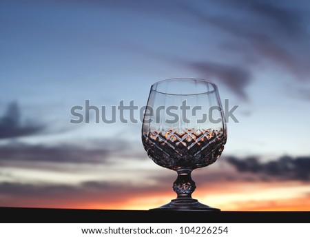 Crystal stem glass against beautiful sunset sky background with copy space.
