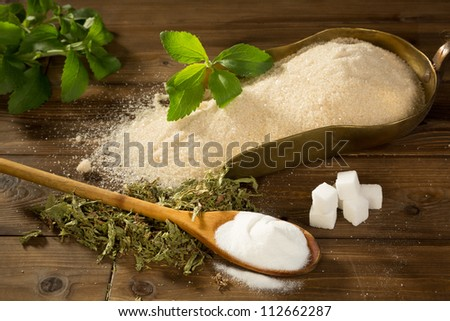 Crystal sugar and lumps together with powder and dried stevia natural sweetener on a wooden table