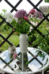 Crystal vase with flowers and a cup of tea on a glass table.