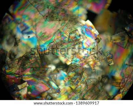 Crystallized liquid crystal under polarized light microscope forming a rainbow texture. Abstract squares filled with rainbow colors. #1389609917