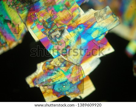 Crystallized liquid crystal under polarized light microscope forming a rainbow texture. Abstract squares filled with rainbow colors. #1389609920
