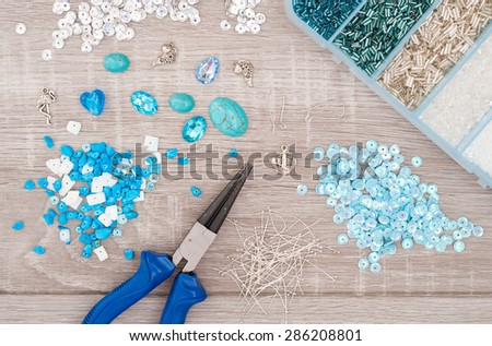 Crystals, pendants, charms, plier, glass hearts, box with beads and accessories to create hand made jewelry on old wooden background. Top view