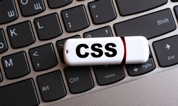 CSS - the word on a white flash drive, lying on a black laptop keyboard. Technology concept