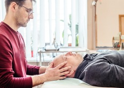 CST therapist uses gentle touch to palpate the synarthrodial joints of the cranium of a male patient, osteopathy and manual therapy