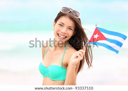 Cuba beach woman holding cuban flag during resort vacation travel on cuba. Beautiful young mixed race Asian Caucasian happy and smiling in bikini.
