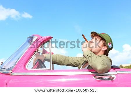 Cuba concept. Vintage car with cigar smoking man with Fidel Castro patrol cap. Funny image cuban conceptual image.