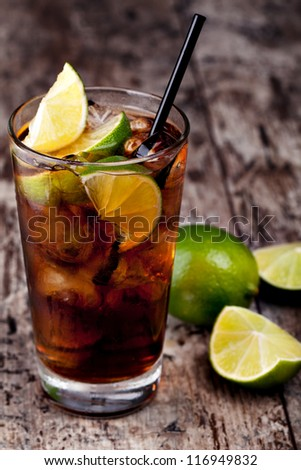Cuba Libre Drink with lime on a wooden table - stock photo