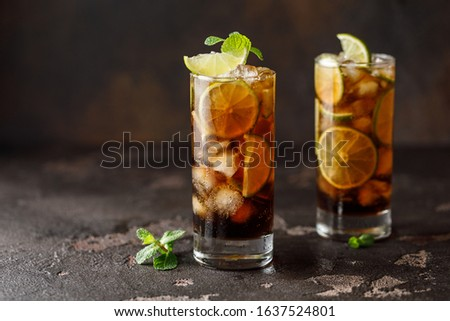 Cuba Libre with brown rum, cola, mint and lime. Cuba Libre or long island iced tea cocktail with strong drinks Photo stock ©