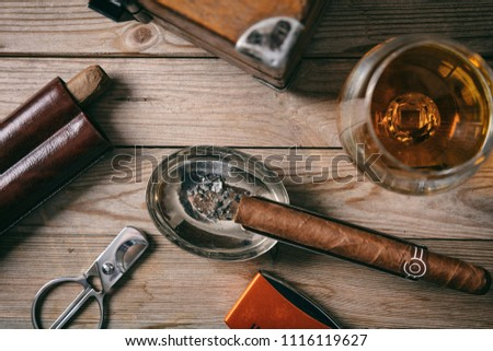 Cuban cigar and a glass of cognac brandy on wooden background, top closeup view