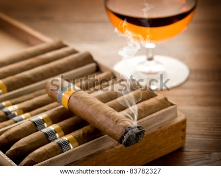 cuban cigar and glass of  liquor on wood background