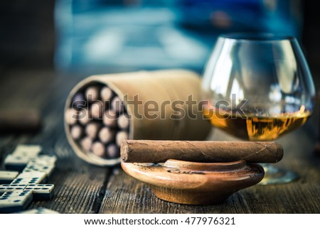 cuban cigar and glass of rum or cognac on wooden table with cuban painting in background